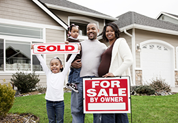 Family holding a sold sign outside their home